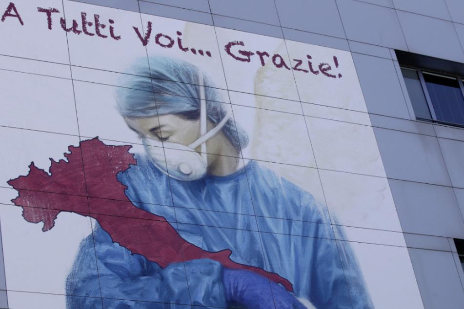 Bergamo: Das riesige Bild einer Zeichnung des venezianischen Künstlers Franco Rivolli zeigt an der Fassade des Krankenhauses Papa Giovanni XXIII. eine Ärztin mit Flügeln auf dem Rücken, die Italien wiegt. Auf Italienisch ist die Aufschrift: «An alle... Danke!» zu lesen. (Archivbild)