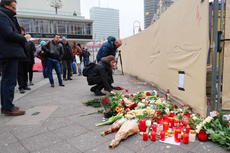 Menschen legen Blumen am Breitscheidplatz in Berlin ab.