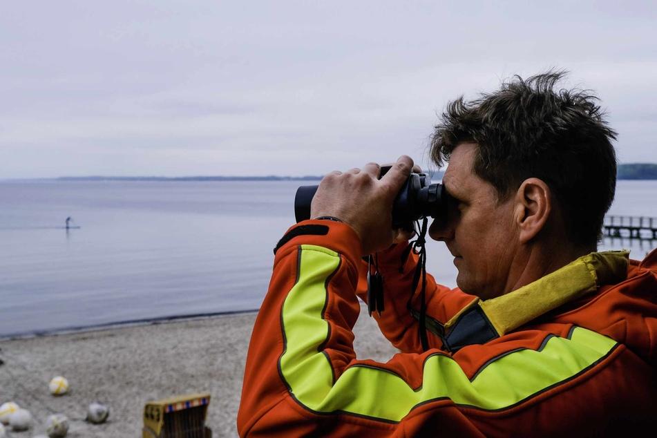 Ein DLRG-Retter schaut durch ein Fernglas auf die Ostsee hinaus. (Symbolbild)