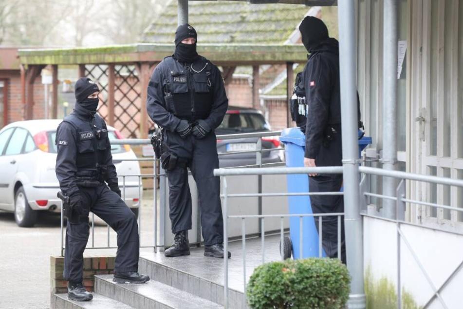 Einsatzkräfte der Polizei stehen während einer Durchsuchung vor einem Haus im Kreis Dithmarschen.