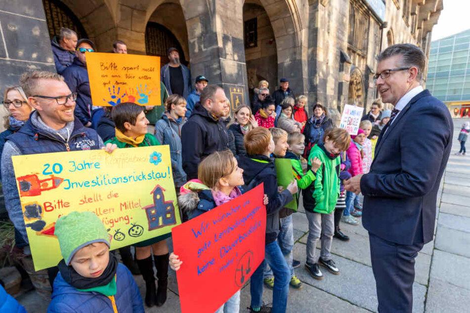 Bürgermeister Ralph Burghart (49, CDU) sprach mit protestierenden Eltern und Schülern vor dem Rathaus. Sie kämpfen für eine grundhafte Sanierung der Grundschule Klaffenbach.