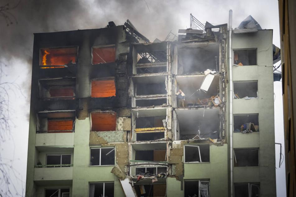 Ein Bewohner steht in einem oberen Stockwerk eines zwölfstöckigen Mehrfamilienhauses, das durch eine Gasexplosion schwer beschädigt wurde, und guckt nach unten.