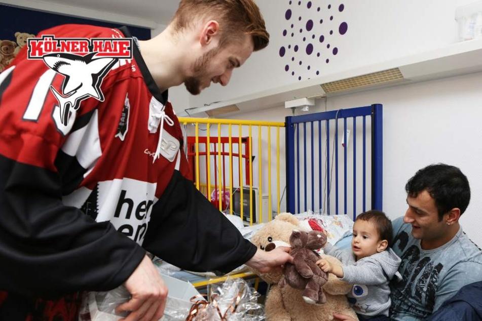 Lucas Dumont (21) von den Kölner Haien beschenkt einen jungen Patienten im Kinderkrankenhaus.