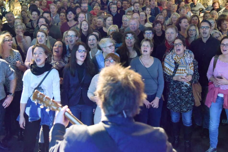 Ein Vorsänger begleitet die hochmotivierte Sänger-Gruppe.