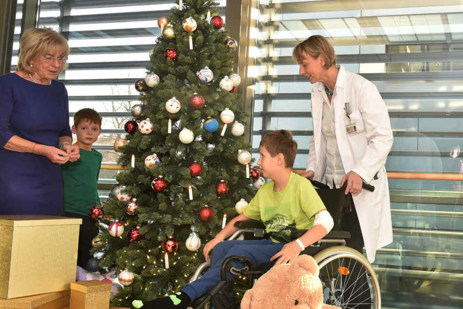 Ursula Herrmann (l.), Und Prof. Angela Hübner schmücken mit den kleinen Patienten Ron (9, r.) und Vincenz (6) den Tannenbaum in der Kinderklinik des Uniklinikums.