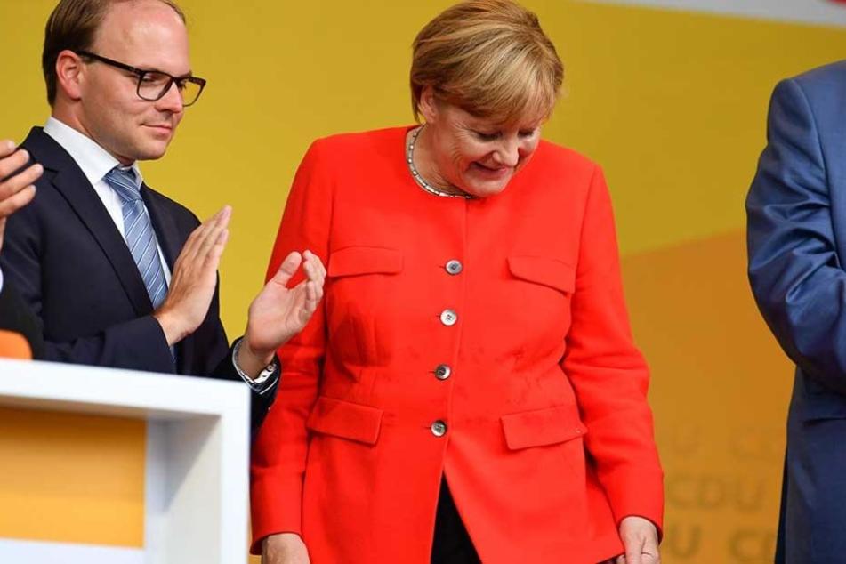 Bundeskanzlerin Angela Merkel schaut auf dem Fleck auf ihrem Sakko, an dem eine Tomate eingeschlagen ist.