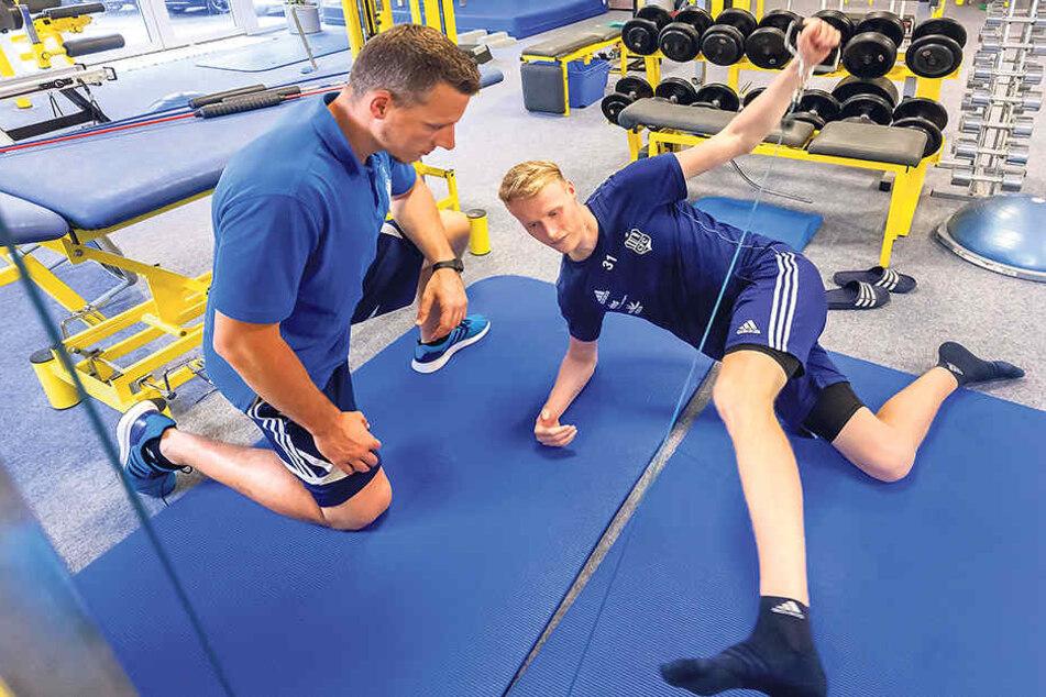 Tom Scheffel mit Sporttherapeut Sebastian Grihm am Seilzugtrainer. Jeden Tag absolviert der verletzte Abwehrspieler Reha-Programm.