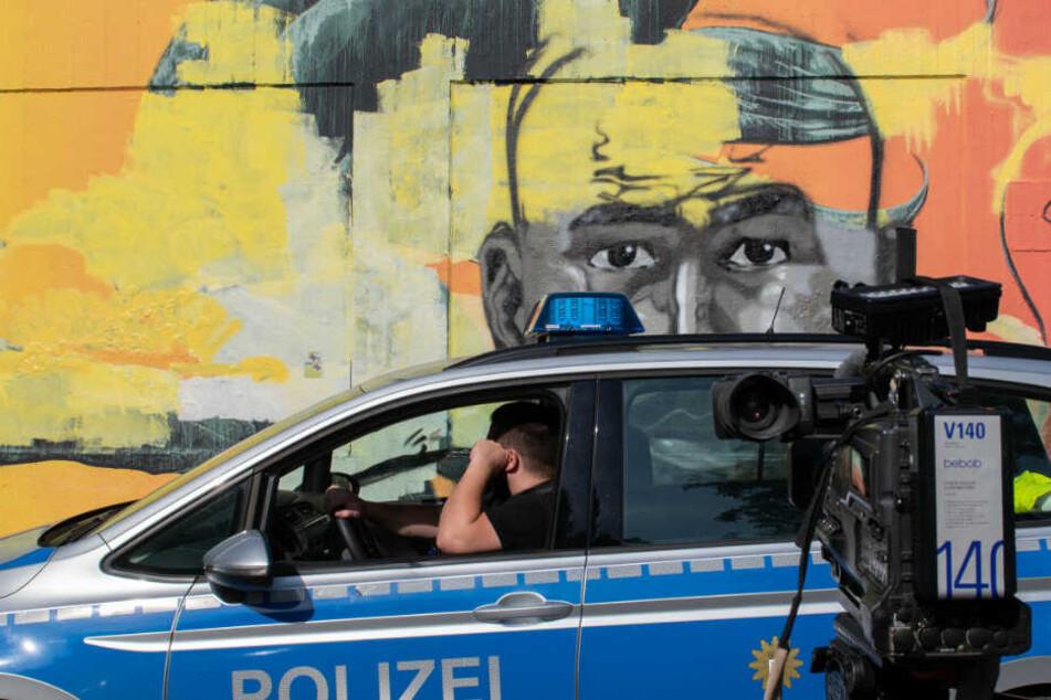 Ein Polizeiwagen steht vor dem Wandbild des ermordeten Nidal R.