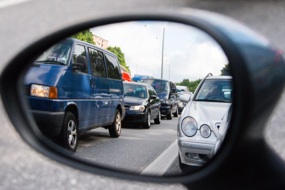 Autos stehen in Hamburg auf der A7 bei Stellingen im Stau und sind dabei im Rückspiegel zu sehen.