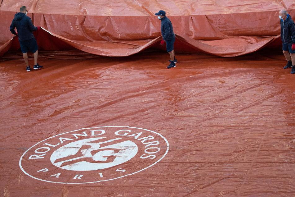 Arbeiter breiten über dem Logo von Roland Garros eine Plane zum Schutz vor Regen über dem Tennisplatz aus. Die French Open beginnen am 27.09.2020.