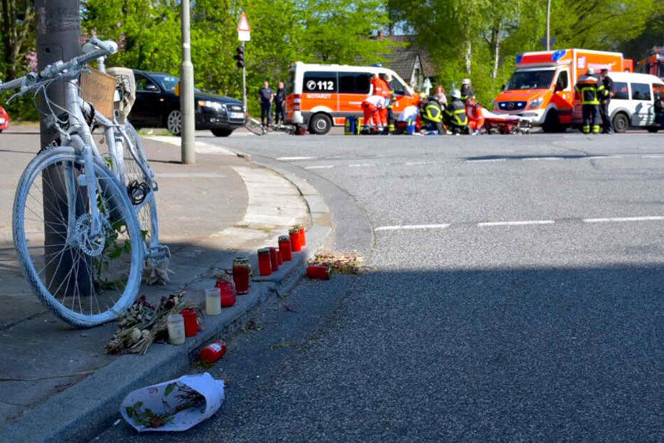 Die kleine Gedenkstätte nach einem tödlichen Radunfall ist im Vordergrund zu sehen, während auf der Unfallkreuzung ein Notarzt einen weiteren verunfallten Fahrradfahrer versorgt.