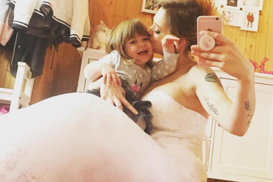 Mit ihrer jüngsten Tochter Juna posiert Anne vor einem Spiegel im Brautkleid.