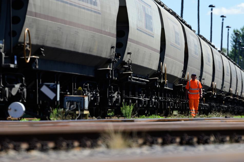 Ein Mann kontrolliert einen Güterzug. Eine junge Frau ist in Osnabrück auf einen Güterzug gesprungen. (Symbolbild)
