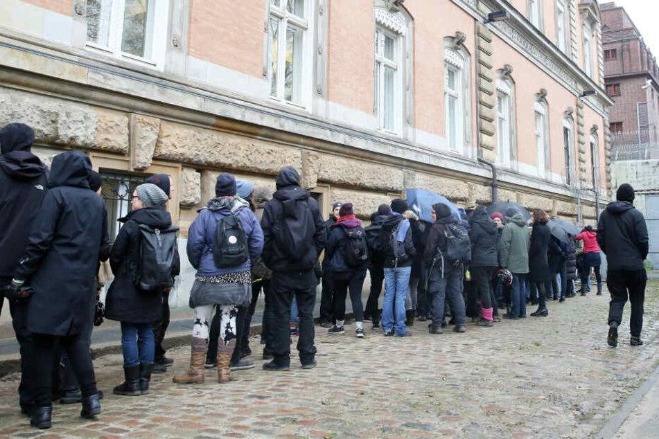 Prozessbesucher warten auf den Zugang zu einem Sitzungsaal, der für Besucher nach einer Kontrolle nur von Außen zu betreten ist.