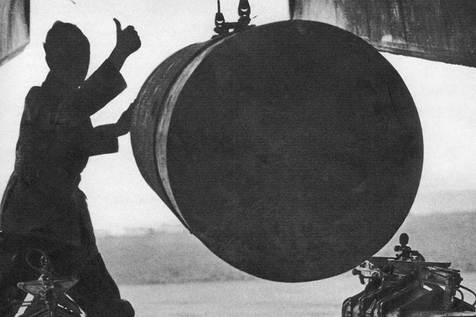 Ein Waffenmeister bringt eine 4.000 Pfund schwere Luftmine, auch Wohnblockknacker genannt, unter dem Bombenschach einer Lancaster in Position.