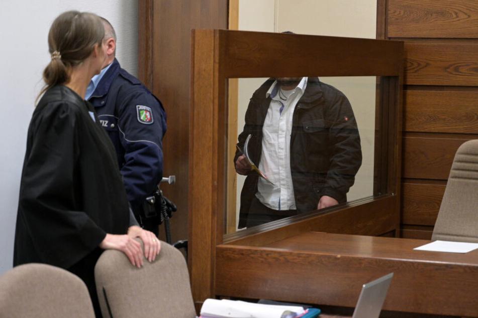 Der Angeklagte (r) kommt in einen Gerichtssaal im Landgericht.