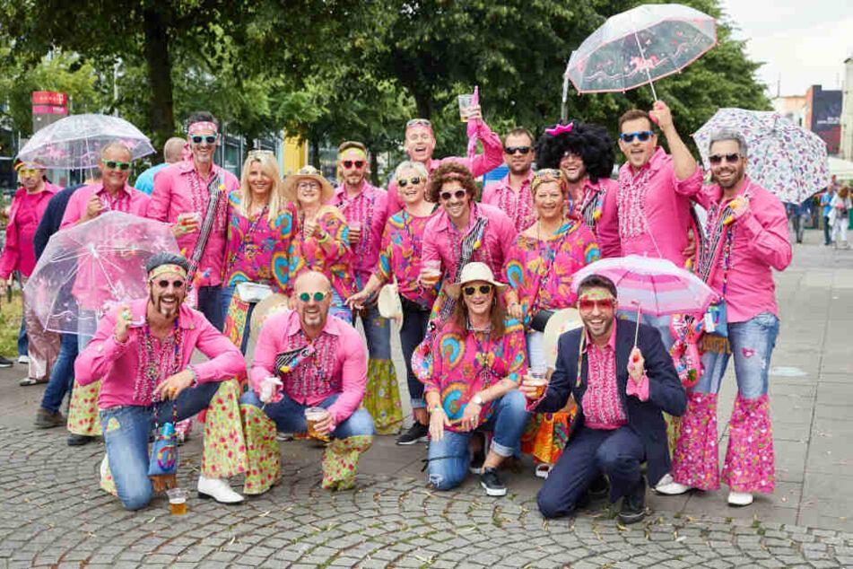Besucher des Schlagermoves posieren in bunten Kostümen und Perücken auf der Reeperbahn.