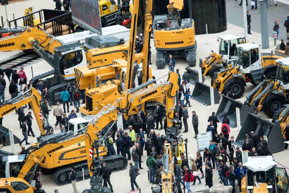 """Besucher gehen während der Baumesse Bauma über den Messestand der Firma """"Liebherr""""."""
