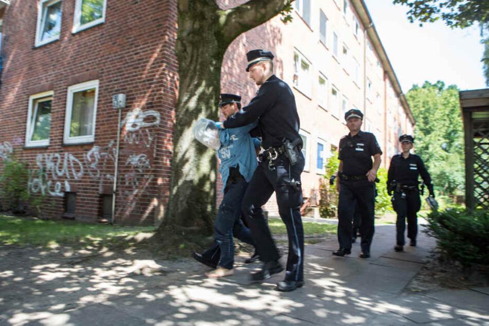 Polizisten führen den Mann ab.