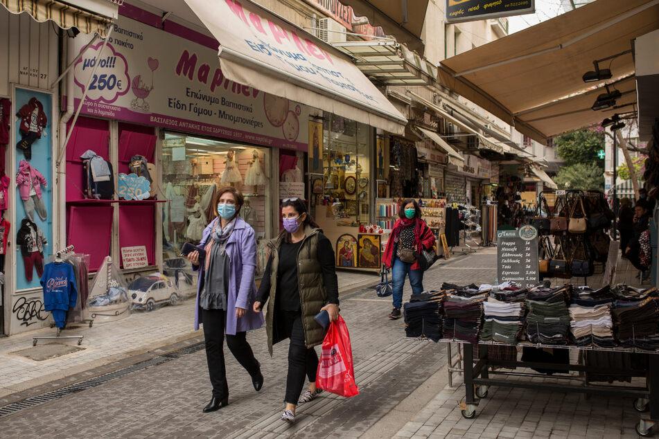 Athen: Zwei Frauen mit Mund-Nase-Bedeckung gehen mit Einkaufstaschen an geöffneten Geschäften in der Innenstadt vorbei.