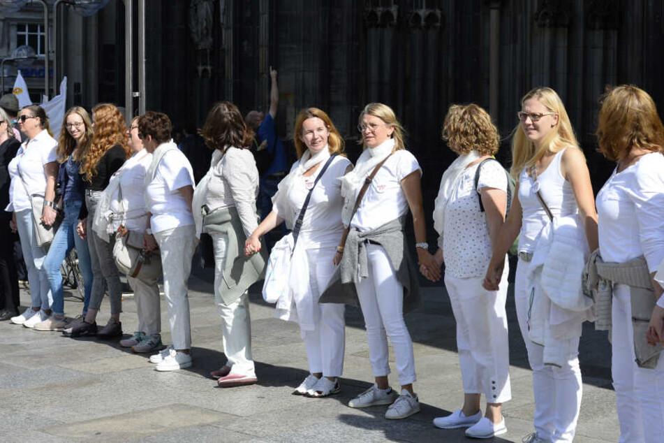 """Unterstützer der Protestbewegung """"Maria 2.0"""" bilden vor dem Kölner Dom eine Menschenkette."""