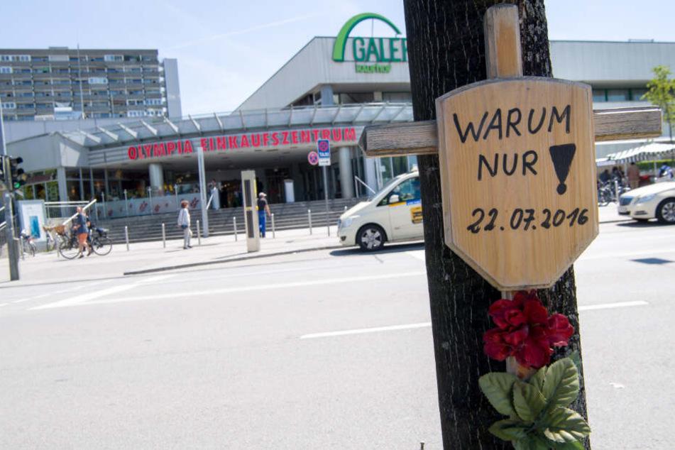 """Ein Holzkreuz mit einem Schild und der Aufschrift """"Warum nur! - 22.07.2016"""" hängt vor dem Eingang zum Olympia-Einkaufszentrum (OEZ). (Archiv)"""
