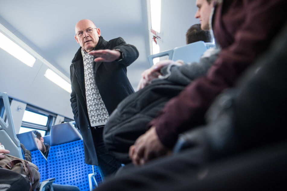 Winfried Hermann diskutiert mit einem Fahrgast.