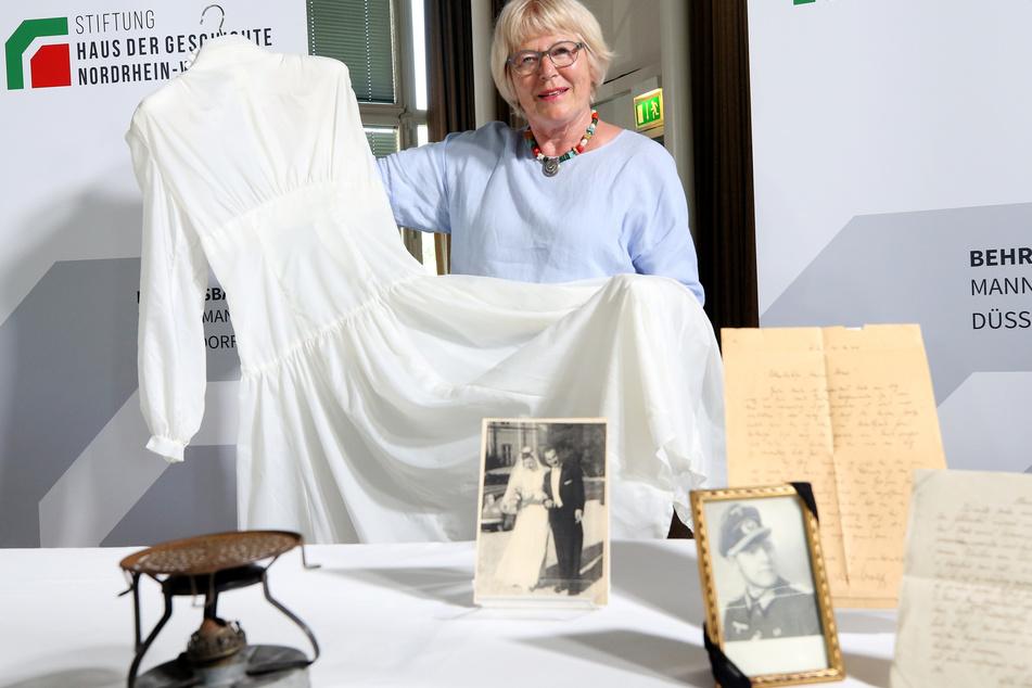 Inge Abresch, Gattin des Sammlungsgründers, zeigt ein Brautkleid aus Fallschirmseide. Das Haus der Geschichte NRW hat die besonderen Schätze angekauft.