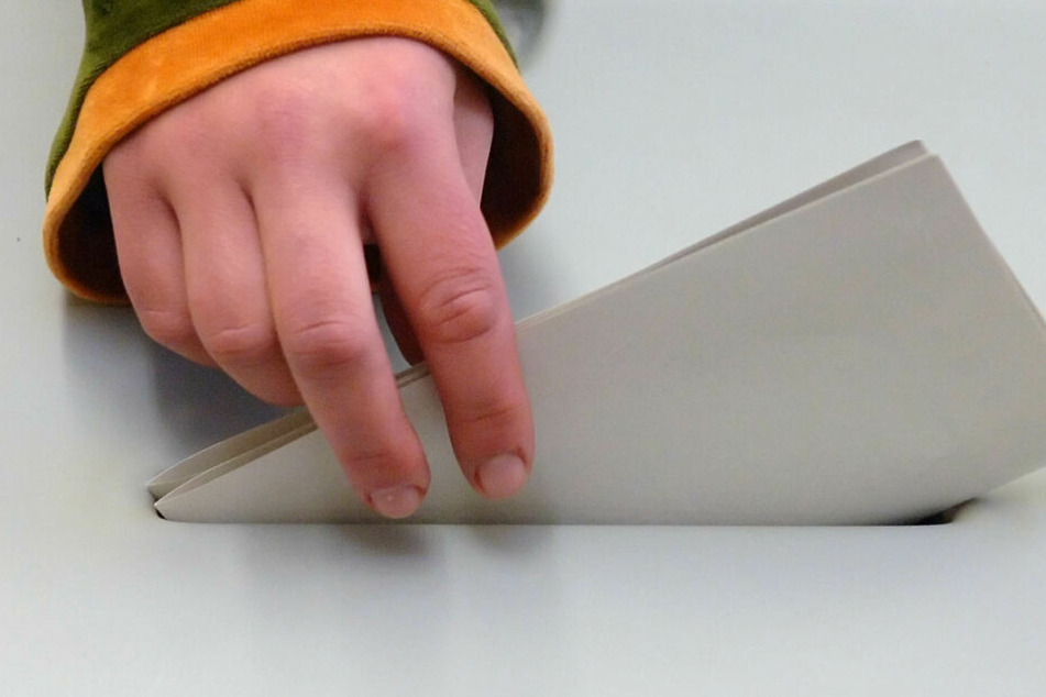 Eine jugendliche Hand steckt einen Stimmzettel in eine Wahlurne.