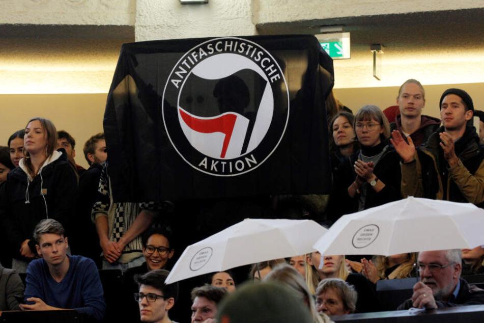 Demonstranten halten im Hörsaal der Uni Hamburg eine Fahne der Antifa hoch.