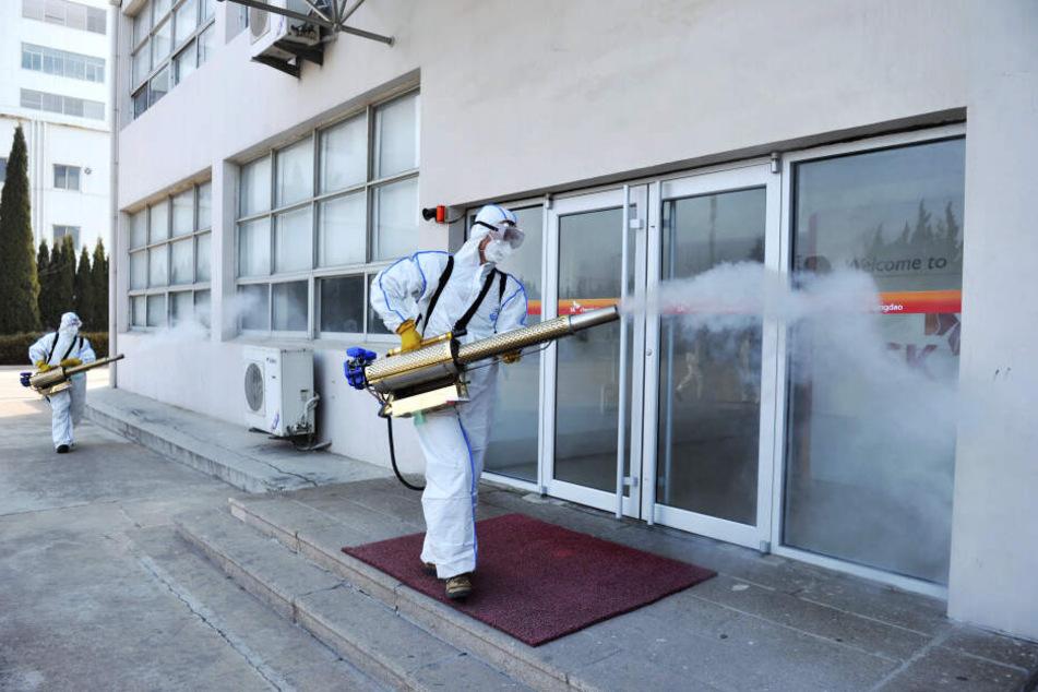 Arbeiter in Schutzkleidung sprühen mit Desinfektionsmittel vor einem Geschäft in China.