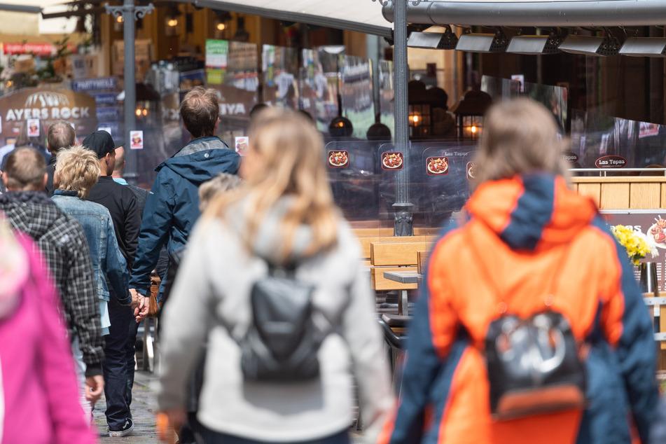 Passanten laufen durch die Münzgasse in der Altstadt an Freisitzen vor Restaurants, die mit Plexiglasscheiben getrennt sind, entlang. Unter strengen Hygieneauflagen darf die Gastronomie im Freistaat seit dem 15. Mai wieder öffnen.