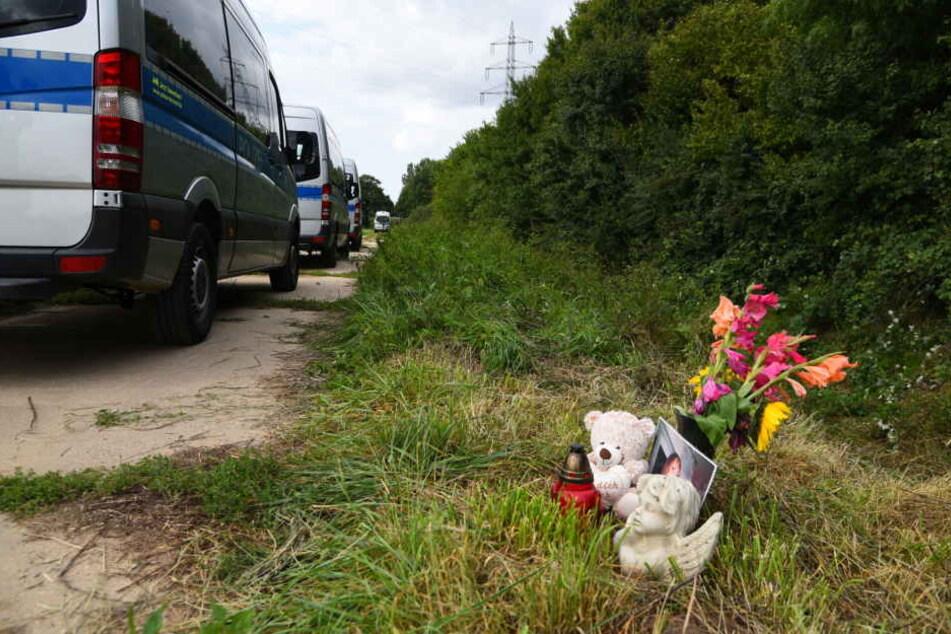 Ein Teddybär und Blumen erinnern am Fundort der Leiche an das Verbrechen.