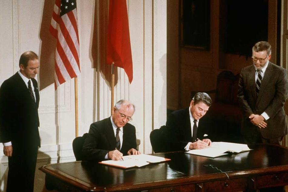 Der damalige US-Präsident Ronald Reagan (r) und der damalige sowjetische Parteichef Michail Gorbatschow unterzeichnen am 8.12.1987 den INF-Vertrag zur Vernichtung der atomaren Mittelstreckenraketen.