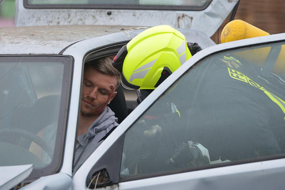 Eine Person ist scheinbar schwer verletzt im Fahrzeug eingeklemmt und muss von Rettungskräften geborgen werden.
