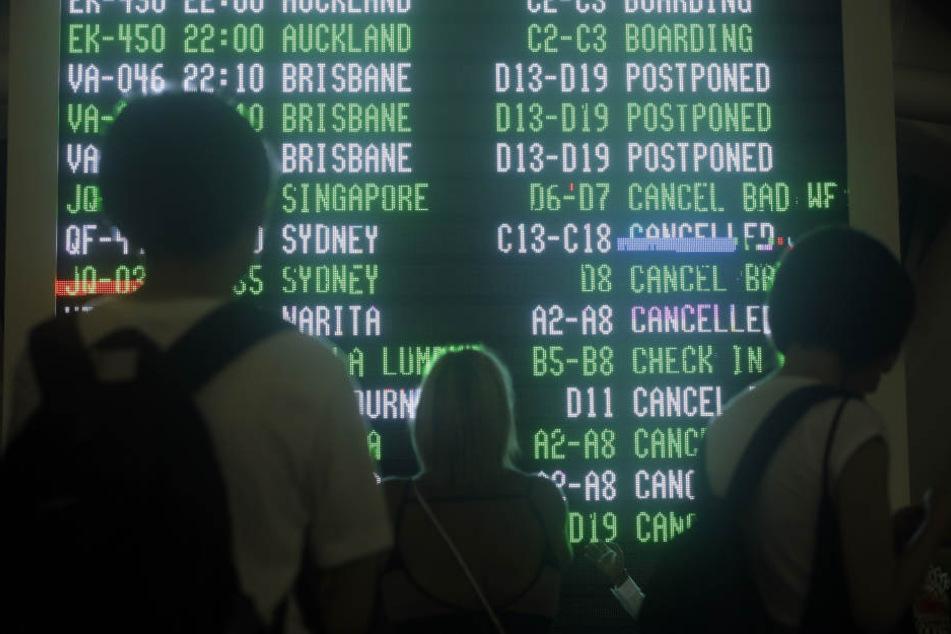 Passagiere schauen auf dem Internationalen Flughafen von Bali auf eine Anzeigetafel, die über zahlreiche ausgefallene Flüge informiert.