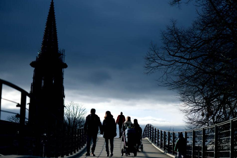 Menschen gehen an Silvester am 31.12.2017 in Freiburg bei Temperaturen um 14 Grad über eine Brücke in der Nähe des Freiburger Münsters. Die Sonne scheint bei frühlingshaften Temperaturen.