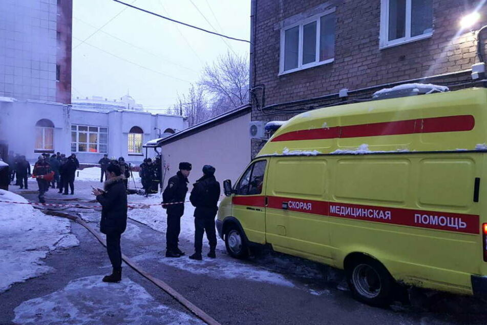 Ein Krankenwagen und Polizisten stehen vor dem Hotel im russischen Perm.