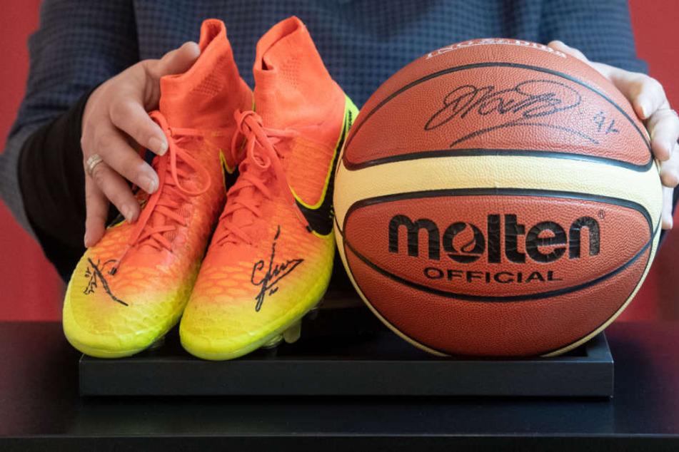 Die Schuhe trug Mario Götze bei der WM 2014 in Brasilien, den Basketball signierte Superstar Dirk Nowitzki.