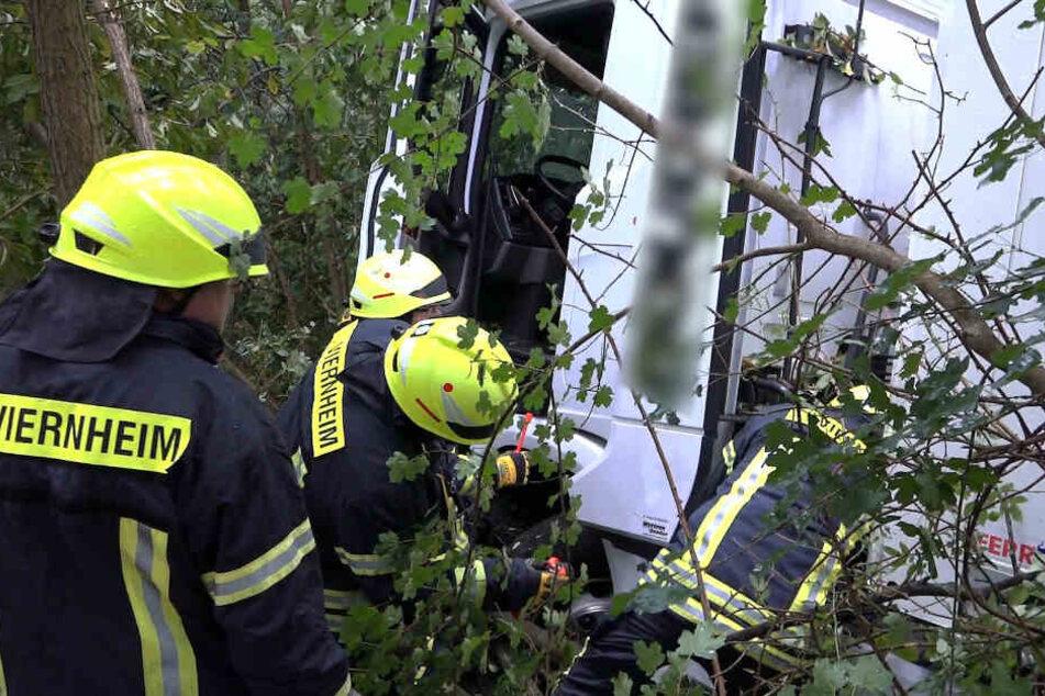 Einsatzkräfte der Feuerwehr inspizieren den Lastwagen.