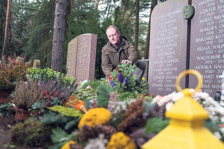 """Heidefriedhof-Chef Mario Fischer (50) kniet vor einer Urnen-Gemeinschaftsanlage. Auf der grünen Wiese """"mit Namensnennung"""" teilen sich 20 Verstorbene ein Grabmal. Ihre Angehörigen platzieren Engel, Fotos und Kerzen."""