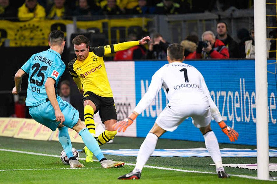 BVB-Stürmer Mario Götze versucht an Freiburgs Abwehrmann Robin Koch (l.) und SCF-Keeper Alexander Schwolow (r.) vorbeizukommen.