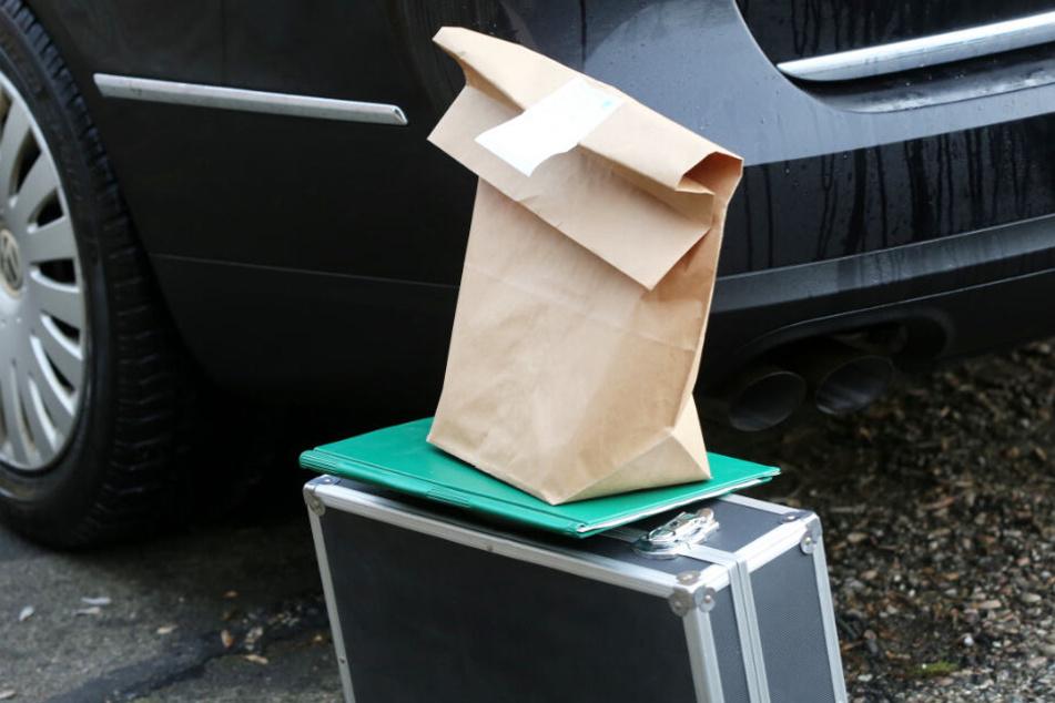 Beweismittel stehen auf einem Koffer mit einer Akte neben einem Auto des Bundeskriminalamtes.