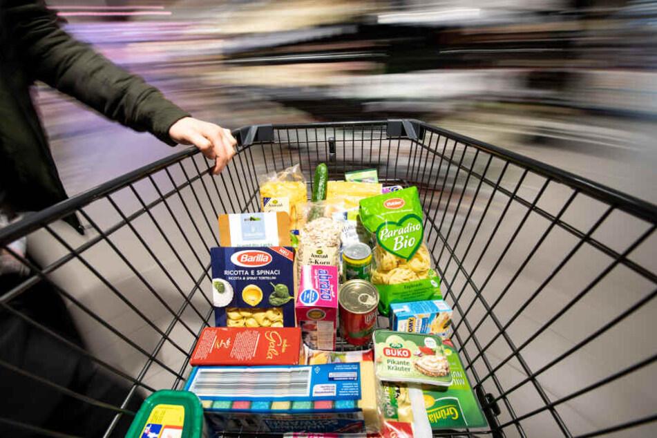 Ein Einkaufswagen wird durch einen Supermarkt geschoben (Symbolbild)
