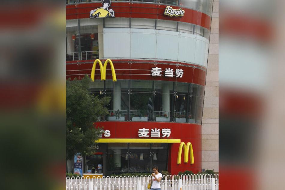"""Die chinesische Fast-Food-Kette """"Zhen Gong Fu"""" wirbt mit einem schwarzhaarigen Mann in gelbem Pullover in Kung-Fu-Pose, der Bruce Lee ähnlich sieht."""