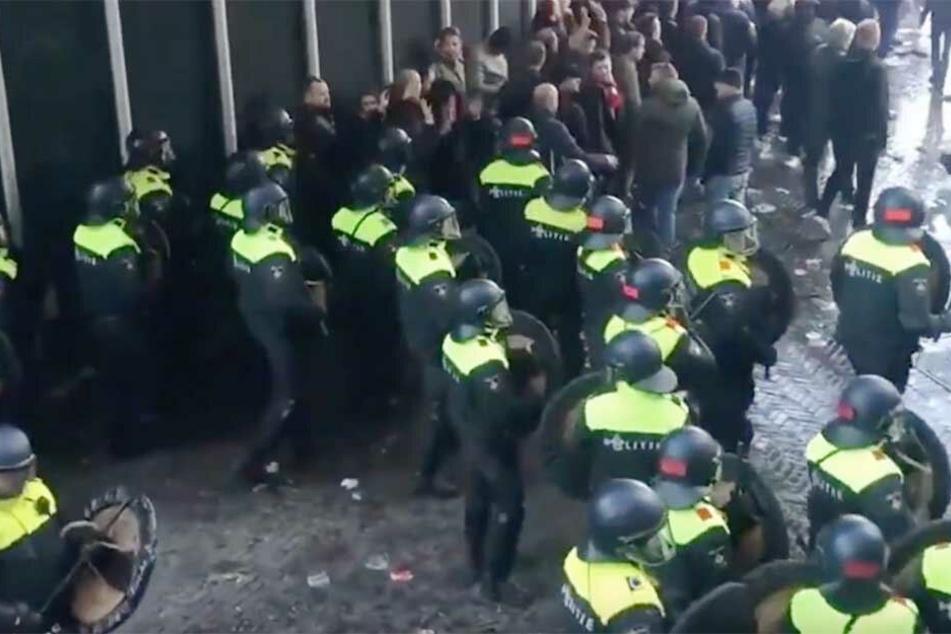 Niederländische Polizei drängt Fußballfans zurück.