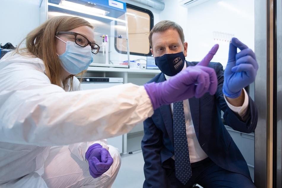 Sachsens Ministerpräsident Michael Kretschmer zusammen mit einer Assistentin des Fraunhofer-Instituts Aachen in einem Prototyp des neuen Corona-Testmobils.