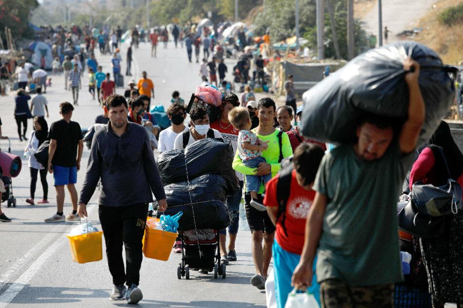 Migranten tragen ihre Habseligkeiten auf einer Straße, die von Moria nach Mytilini führt.