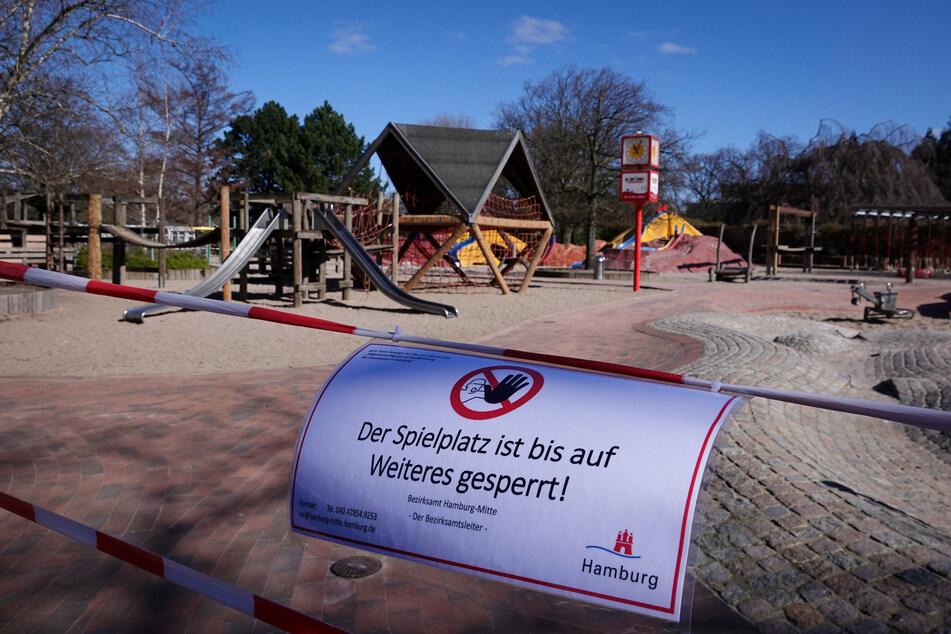 """Ein Schild hängt an einem Absperrband am Eingang zum großen Spielplatz im Park """"Planten un Blomen""""."""