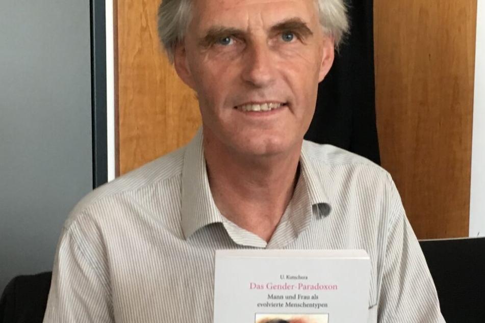 """Der Wissenschaftler Ulrich Kutschera zeigt im Gerichtssaal sein Buch """"Das Gender-Paradoxon""""."""
